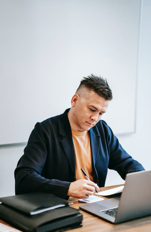 Photo Of Man Writing On Paper