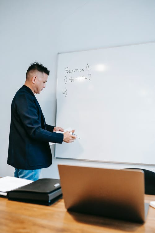 Photo Of Man Standing In Front Of Whiteboard