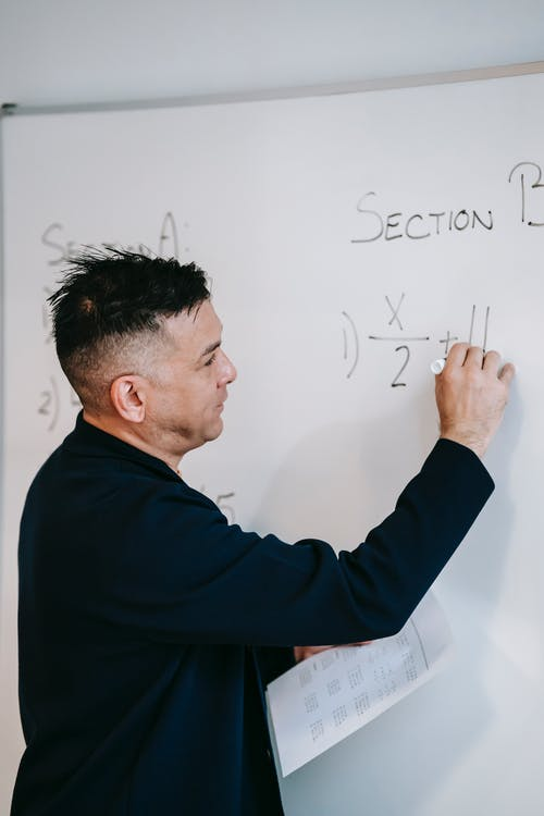 Photo Of Teacher Writing On Whiteboard