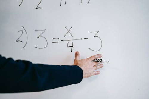 Photo Of Person Teaching On White Board