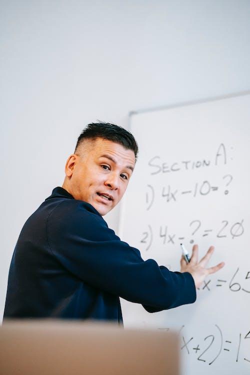 Photo Of Man Teaching On White Board