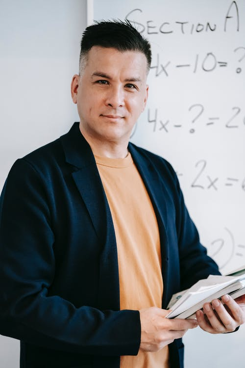 Photo Of Man Standing In Front Of White Board