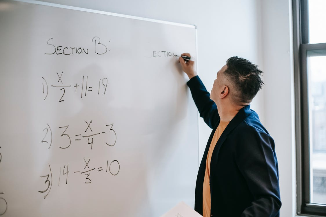 Focused worker writing equations on whiteboard in office in daytime