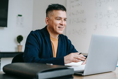 Photo Of Man Looking Happily On His Laptop