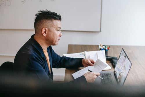 Side view of serious adult guy in casual clothes sitting on chair at table and having video call on netbook with colleague with papers and pen in light room