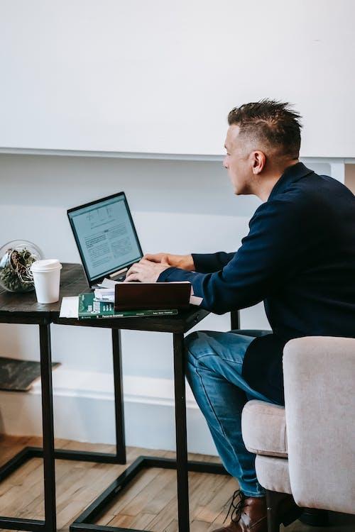 Uomo In Maglione Nero Utilizzando Computer Portatile Nero