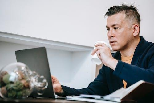 Uomo In Maglione Blu Utilizzando Il Computer Portatile