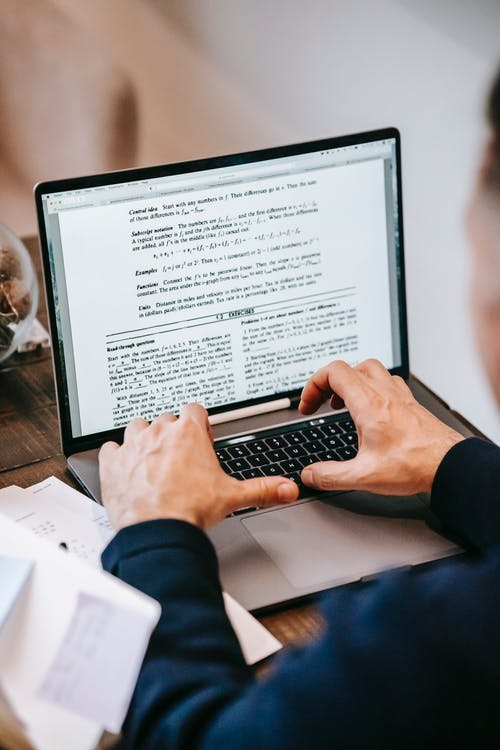 Persona Che Utilizza Macbook Pro Sulla Tavola Di Legno Marrone