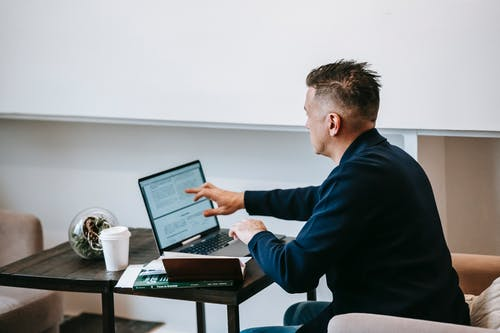 Photo Of Man Using His Laptop On Top Of Wooden Table