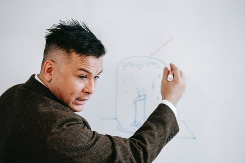 Photo Of Man Teaching On White Board