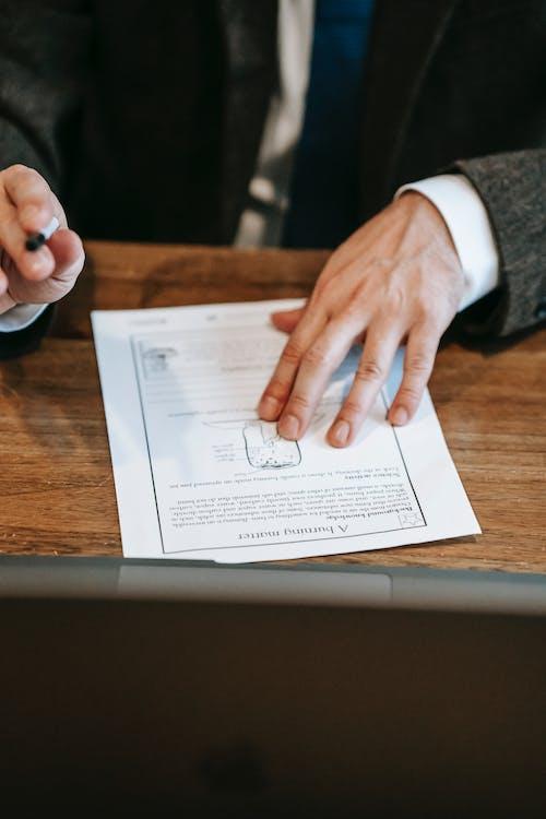 茶色の木製テーブルに白いプリンター用紙を持っている人