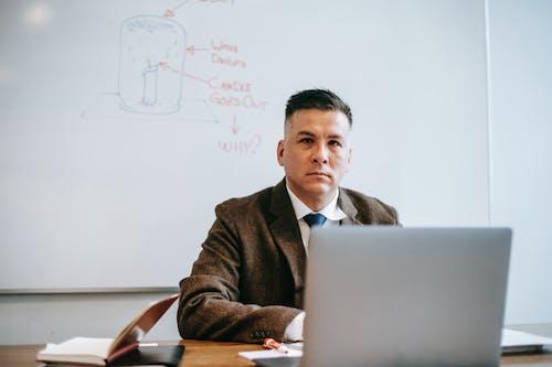 Man In Black Suit Jacket Menggunakan Macbook