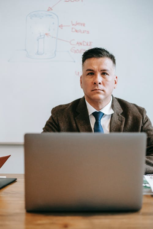 Photo Of Man Sitting In Front Of Gray Laptop