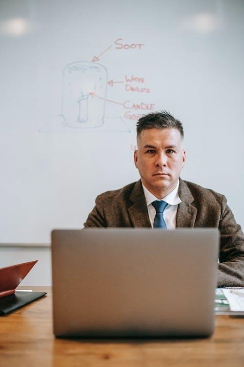 Man In Brown Suit Jacket Menggunakan Macbook