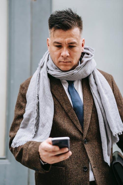 Pria Dengan Syal Abu Abu Dan Mantel Coklat Memegang Smartphone Hitam