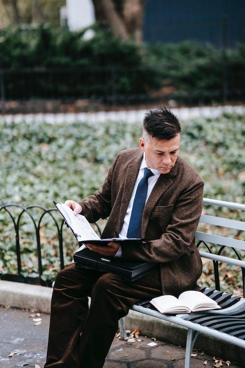 Homem De Paletó Marrom E Calça Preta Sentado No Banco Lendo Um Livro