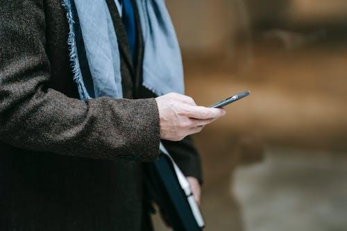Pria Jas Hitam Memegang Smartphone Hitam