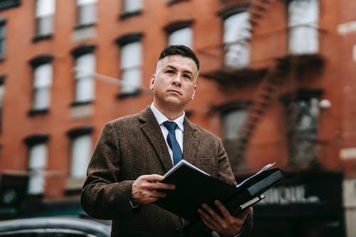 Homem De Paletó Marrom Segurando Um Computador Tablet