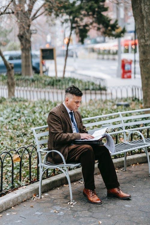 Mann In Der Schwarzen Jacke, Die Auf Weißer Bank Sitzt