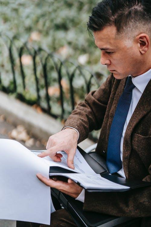 Homme En Manteau Marron à L'aide D'un Ordinateur Portable Blanc