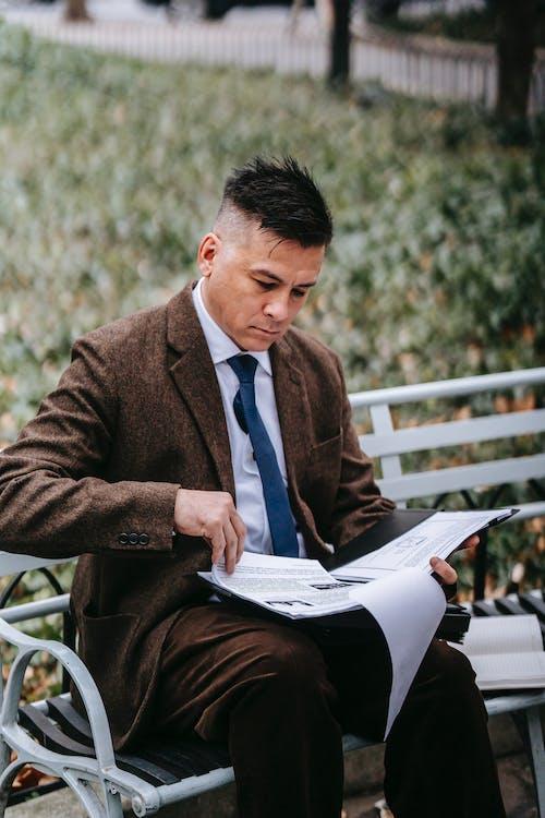 Mann In Brauner Anzugjacke, Die Auf Weißem Bank Lesebuch Sitzt