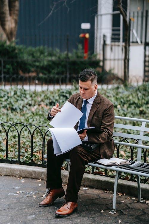 Homem De Terno Marrom Sentado No Banco Lendo Um Livro