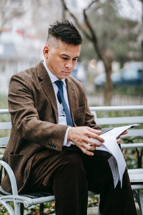 Mann In Brauner Anzugjacke, Die Auf Weißem Plastiksessel Sitzt