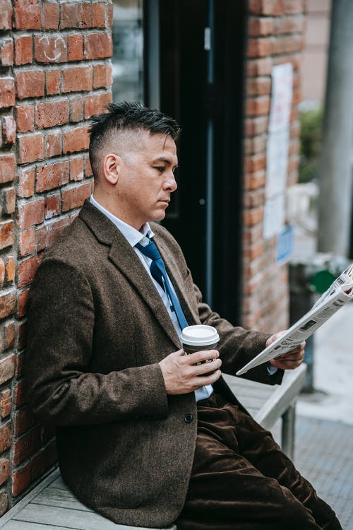 Photo Of Man Reading Newspaper While Holding Drink