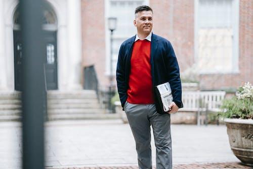 Buku Memegang Pria Berkemeja Merah Biru Lengan Panjang Dan Celana Abu Abu