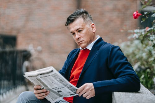 Photo Of Man Reading Newspaper While Leaning On Concrete Surface