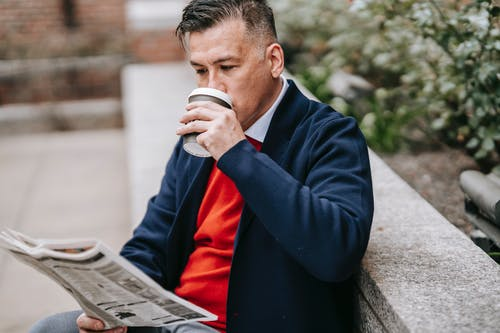 Photo Of Man Reading Newspaper While Drinking Coffee
