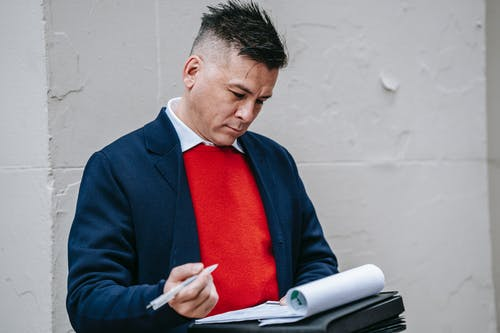 Photo Of Man Carrying Pen And Documents