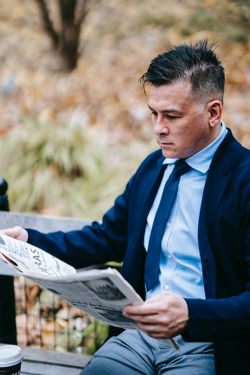 Photo Of Man Reading Newspaper