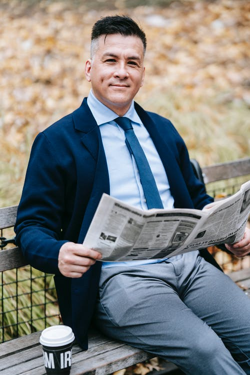 Photo Of Man Holding Newspaper While Sitting On A Wooden Bench