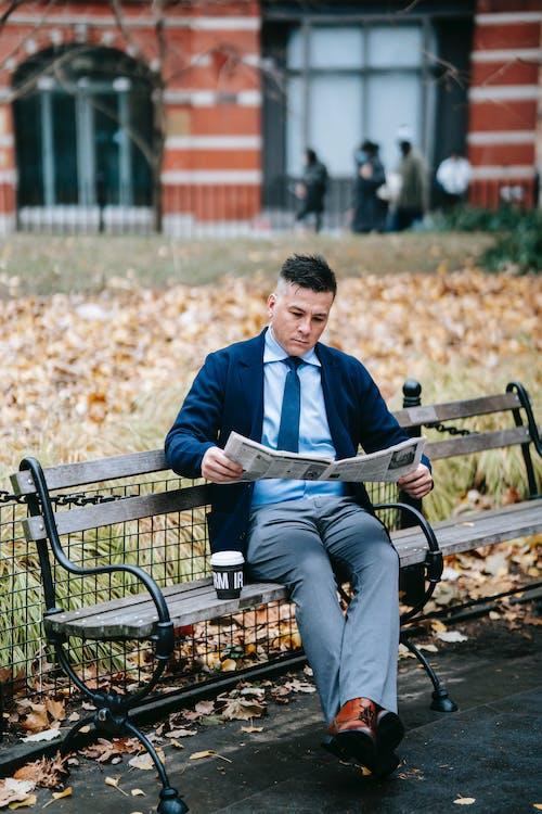 Photo Of Man Reading Newspaper On Park