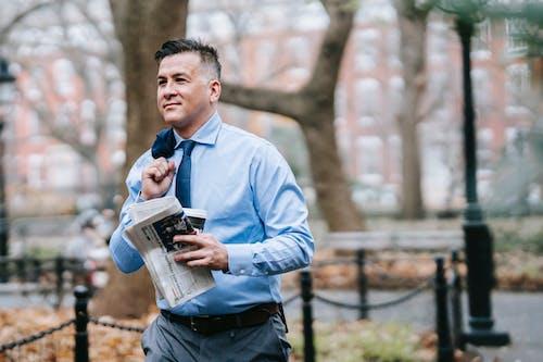 Pria Berbaju Biru Membaca Koran