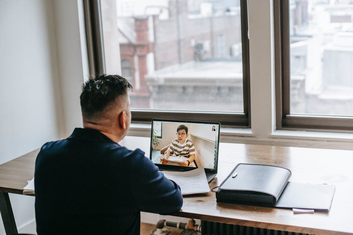 Back view of male in casual clothes sitting at table on chair while having video chat on laptop with pupil near papers and briefcase in light apartment near window