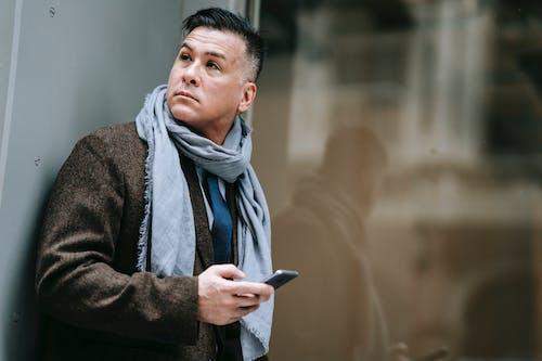 Homem De Casaco Marrom Segurando Um Smartphone Preto