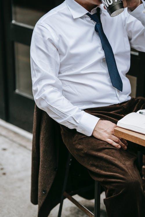Homem De Camisa Branca E Calça Marrom Sentado Em Um Banco De Madeira Marrom