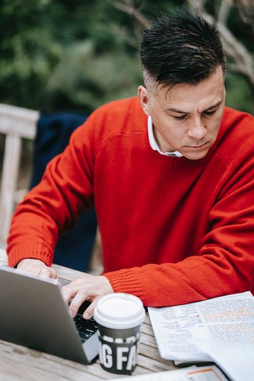 Homem De Suéter Vermelho Usando Macbook