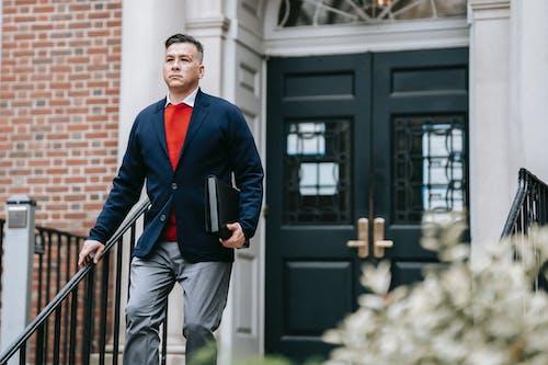 Homem De Paletó Azul E Calça Cinza Segurando Um Smartphone Preto