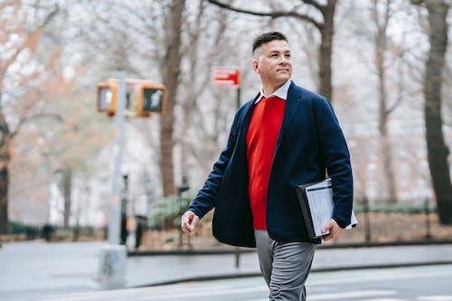 Homem De Jaqueta Preta E Vermelha E Calça Cinza Segurando Um Livro