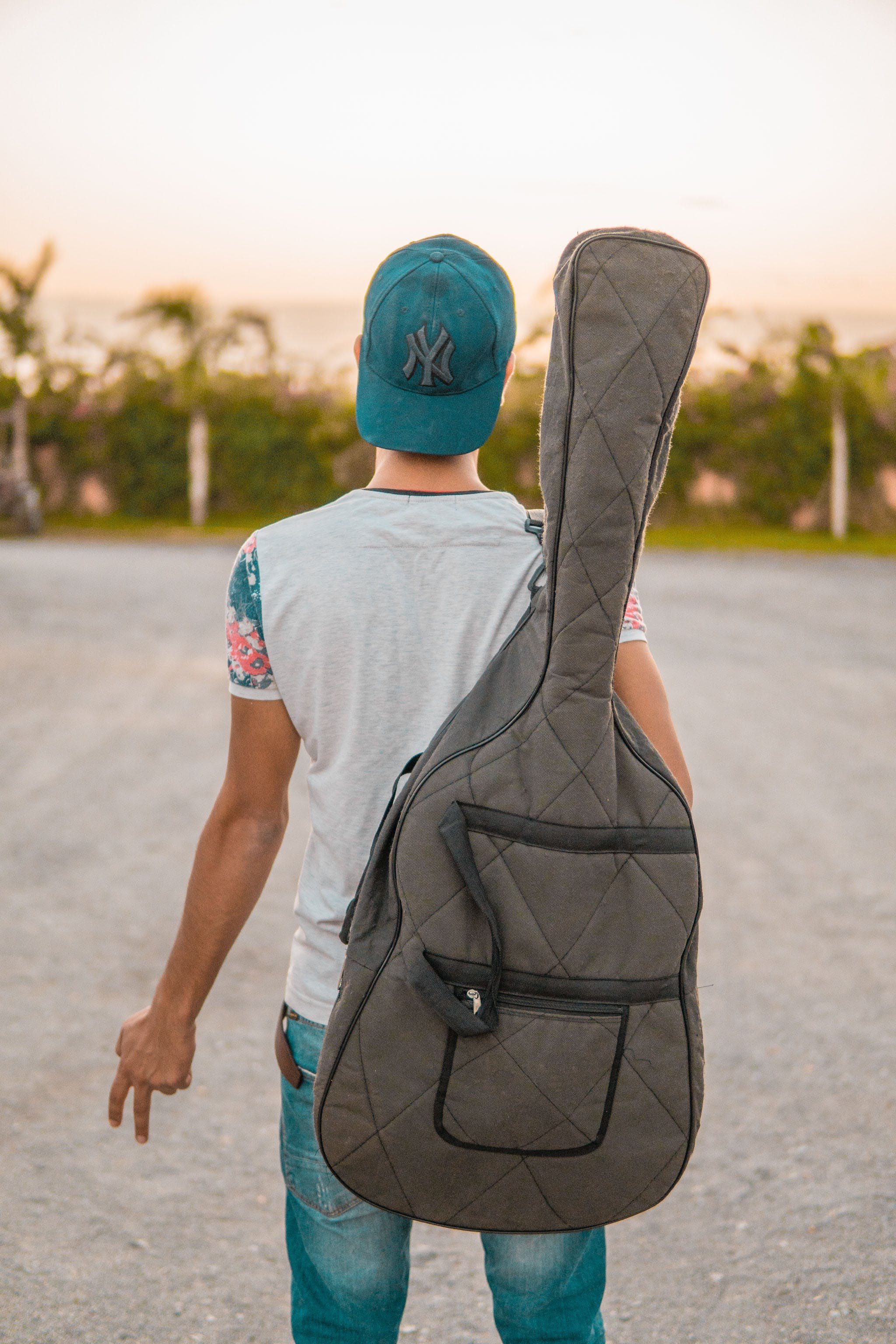Selective Focus Photography of Man Holding Gig Bag
