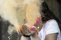 Woman in White Cap-sleeved Shirt Blowing Dust