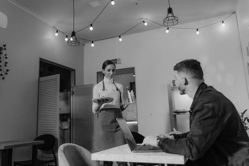Man in Black Jacket Using Laptop Inside A Cafeteria With A Woman Serving Food