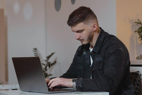 Man in Black Denim Jacket Using Laptop