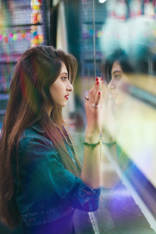 Calm ethnic woman standing near glass wall