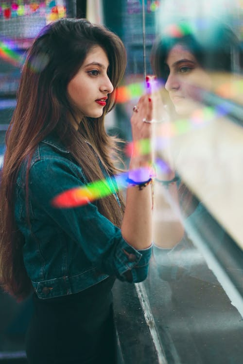 Side view of focused ethnic female standing near glass wall and observing bowling alley while spending time in modern amusement center on blurred background
