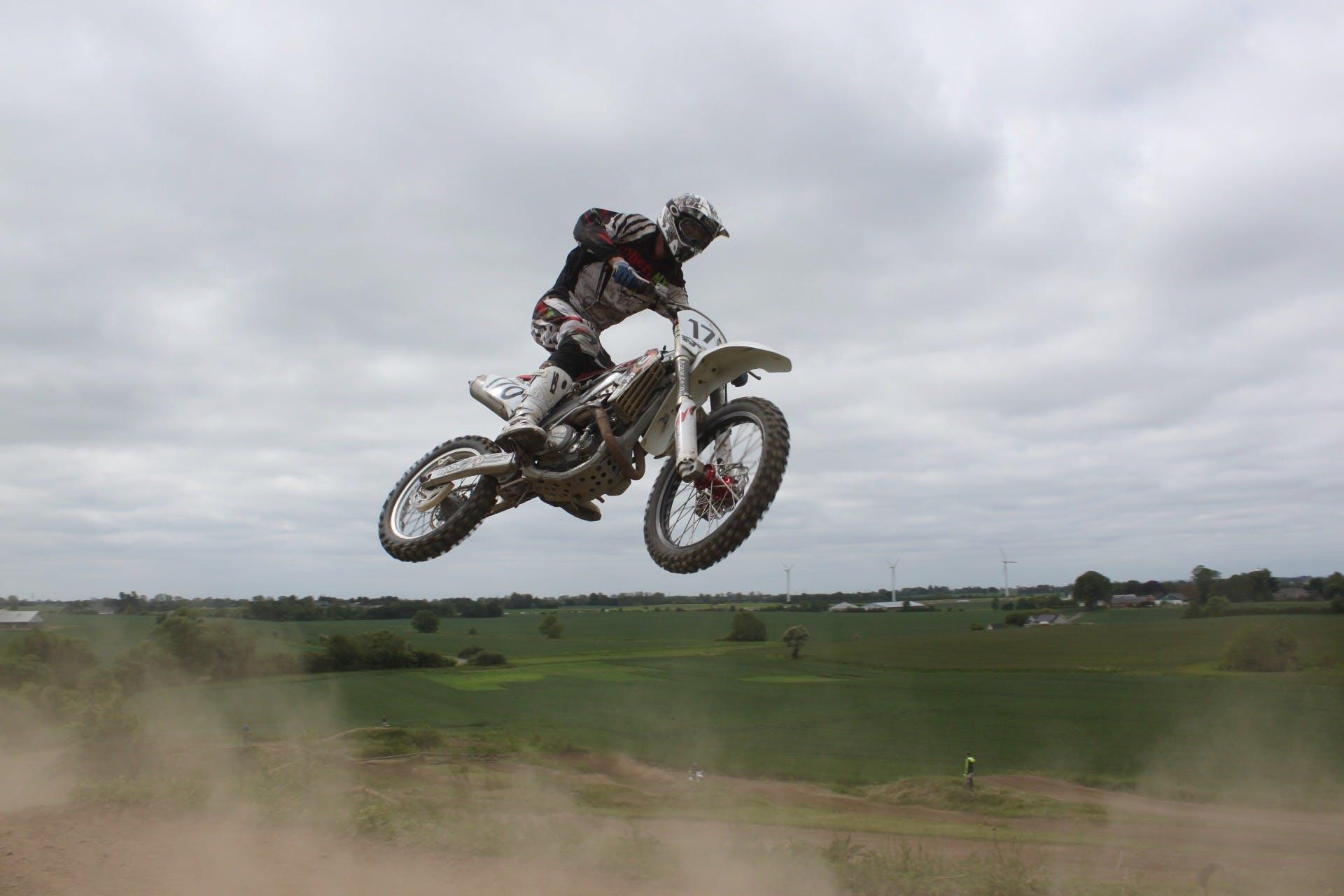 Man Riding Moto Cross Bike Doing Tricks Mid Air Under Cloudy Skies during Daytime