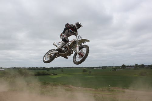 Man Riding Moto Cross Bike Doing Tricks Mid Air Under Cloudy Skies during Daytime
